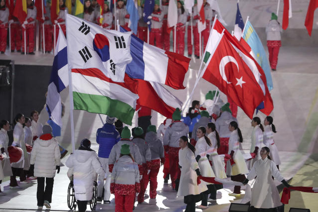 Athletes carry their national flags to take part in the closing ceremony of the 2018 Winter Paralympics in Pyeongchang, South Korea, Sunday, March 18, 2018. Beijing will host the 2022 Winter Paralympics. (AP Photo/Ng Han Guan)