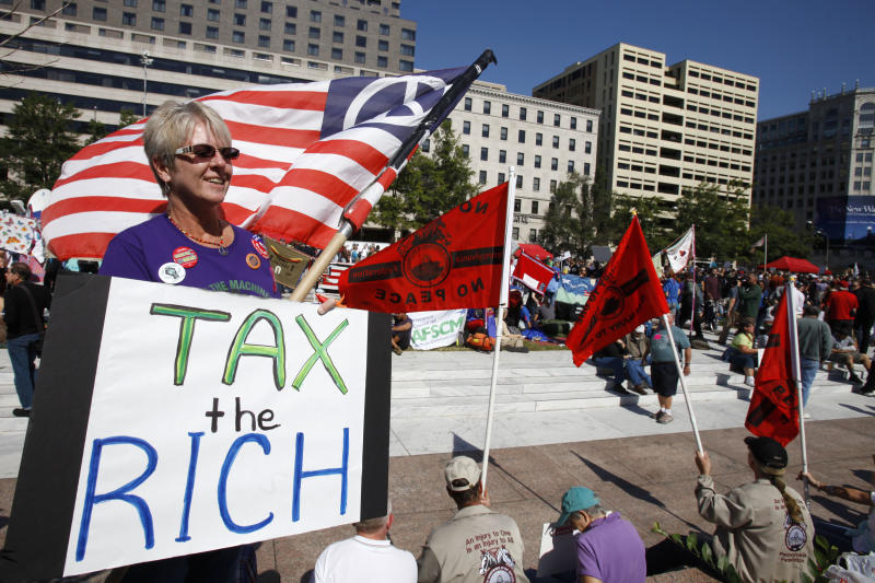 "FILE - In this Oct. 6, 2011 file photo, Carol Gay, of Brick, N.J., holds a sign saying ""Tax the Rich,"" as several groups including the Peoples Uprisings, October 2011 Coalition, and Occupy DC, ""occupy"" Freedom Plaza in Washington. The income gap between the rich and everyone else is large and getting larger, while middle-class incomes stagnate. That's raised concerns that the nation's middle class isn't sharing in economic growth as it has in the past. And it sparked the Wall Street protests that spread to other cities in the country. (AP Photo/Jacquelyn Martin, File)"
