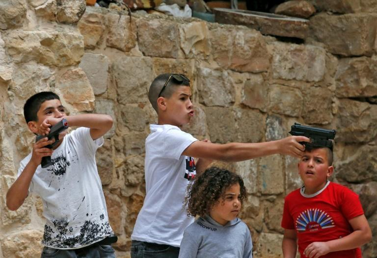 Palestinian children play with plastic toy guns on the first day of Eid al-Fitr, the Muslim holiday at the end of the holy fasting month of Ramadan, in the flashpoint city of Hebron in the occupied West Bank on May 24