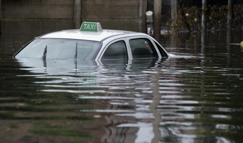 A taxi is submerged in floodwaters in La Plata, in Argentina's Buenos Aires province, Wednesday, April 3, 2013. At least 35 people were killed by flooding overnight in Argentina's Buenos Aires province, the governor said Wednesday, bringing the overall death toll from days of torrential rains to at least 41 and leaving large stretches of the provincial capital under water. (AP Photo/Natacha Pisarenko)