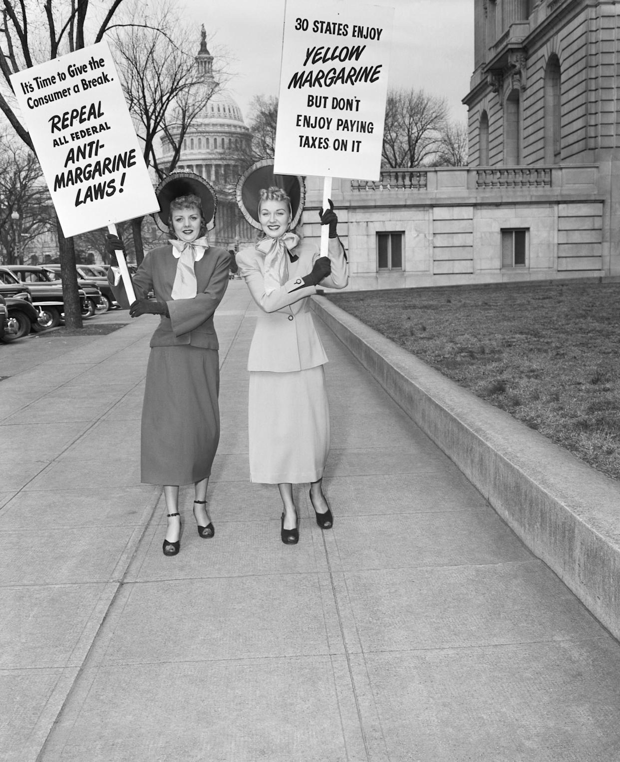 Two housewives in gay blue bonnets, Mrs. J.C. Alicoate (L) of Miami, and Mrs. Arthur Hebb, Jr. of Baltimore, add their bit towards the fight for repeal of the tax on oleomargarine. They parade with their signs near the Capitol in Washington, D.C. on March 3, 1949.