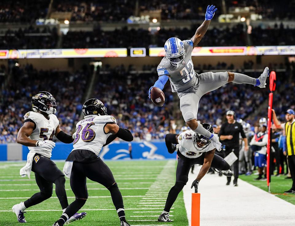 Lions running back D'Andre Swift jumps over Ravens safety Chuck Clark (36) and cornerback Brandon Stephens (21) during the second half of the Lions' 19-17 loss at Ford Field on Sunday, Sept. 26, 2021.