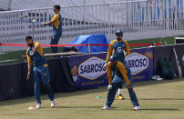 Pakistan players, Imad Wasim, left, throws the ball while teammates Haris Sohail, center front, and Babar Azam watch during a practice session at the Pindi Cricket Stadium, in Rawalpindi, Pakistan, Thursday, Oct. 29, 2020. The Zimbabwe cricket team is in Pakistan to play three ODIs and three Twenty20 International match series, beginning with the first ODI on Friday. (AP Photo/Anjum Naveed)