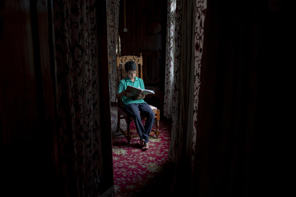 """Mohsin Shafi holds a book and sits for a photograph inside their houseboat on the Dal Lake in Srinagar, Indian controlled Kashmir, Wednesday, July 22, 2020. Schools in the disputed region reopened after six months in late February, after a strict lockdown that began in August 2019, when India scrapped the region's semi-autonomous status. In March schools were shut again because of the coronavirus pandemic. """"We are not able to keep up with lessons online and we miss our regular school,"""" he said. (AP Photo/Dar Yasin)"""