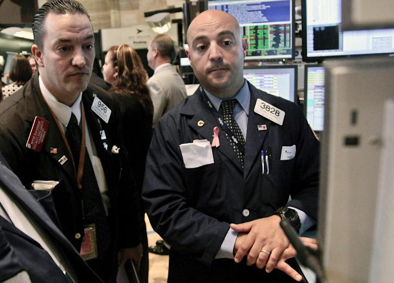 FILE - In this June 6, 2012 file photo, Wellington Shields' Theodore Nelson, left, and Knight Capital's Frank Babino, right, work on the floor of the New York Stock Exchange. U.S. stock futures are following markets higher across the globe Monday, June 11, 2012, after the European Union said it would lend Spain as much as $125 billion to save its banks. (AP Photo/Bebeto Matthews, File)