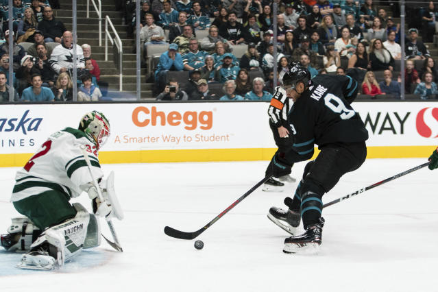 Minnesota Wild goaltender Alex Stalock (32) deflects a shot by San Jose Sharks' Evander Kane (9) during the first period of an NHL hockey game Thursday, Nov. 7, 2019, in San Jose, Calif. (AP Photo/John Hefti)