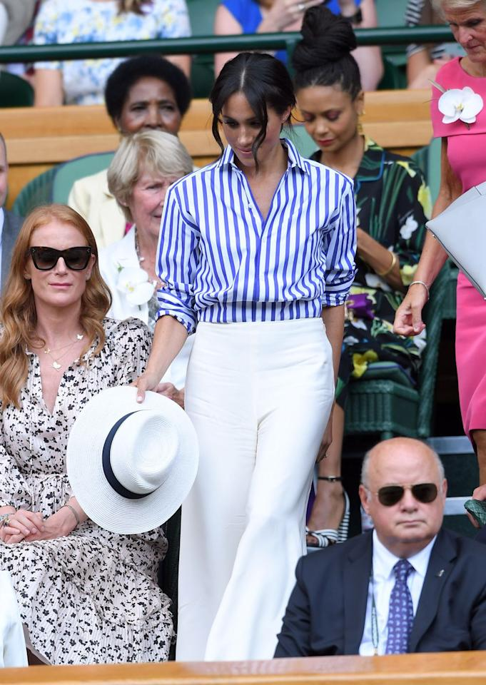 <p>For her first Wimbledon appearance as a royal, Meghan wore a blue striped shirt and white wide leg trousers by Ralph Lauren. Although she had her favourite Panama hat, Meghan was unable to wear it as hats are banned in the royal box.</p>