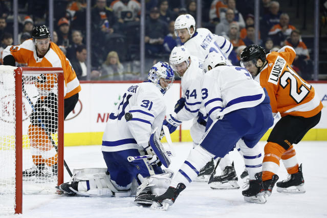 Philadelphia Flyers' Scott Laughton (21) scores a goal past Toronto Maple Leafs' Frederik Andersen (31) as Justin Holl (3) and Morgan Rielly (44) defend during the second period of an NHL hockey game, Tuesday, Dec. 3, 2019, in Philadelphia. (AP Photo/Matt Slocum)