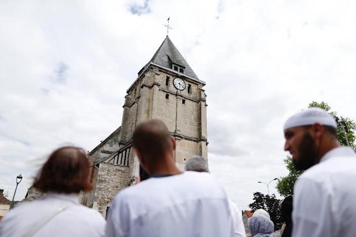 Muslims put flowers and hold a minute of silence on July 29, 2016 in front of the church if Saint-Etienne-du-Rouvray, western France, where French priest Jacques Hamel waskilled on July 26 in the church during a hostage-taking (AFP Photo/Charly Triballeau)