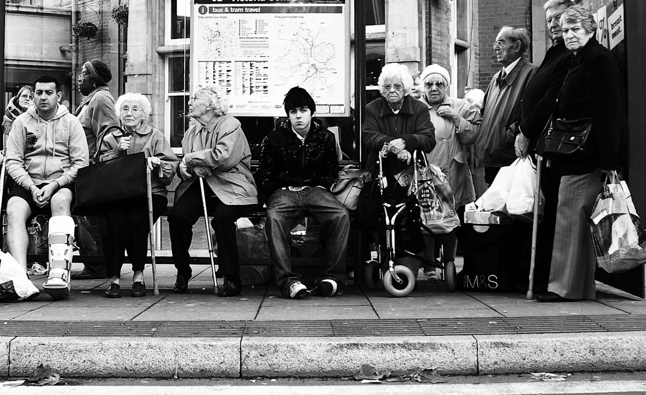 'Bus Stop': A bus stop in the UK is full of elderly people looking for a seat, but a young teenage boy refuses to give up his (Stephen Wright)