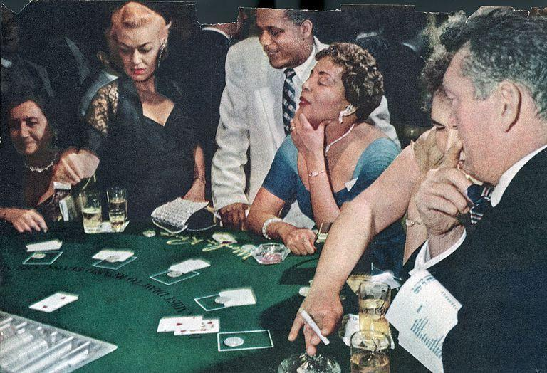 <p>Patrons trying their luck at the blackjack table in the Moulin Rouge casino. Sadly, the casino closed in 1955.</p>