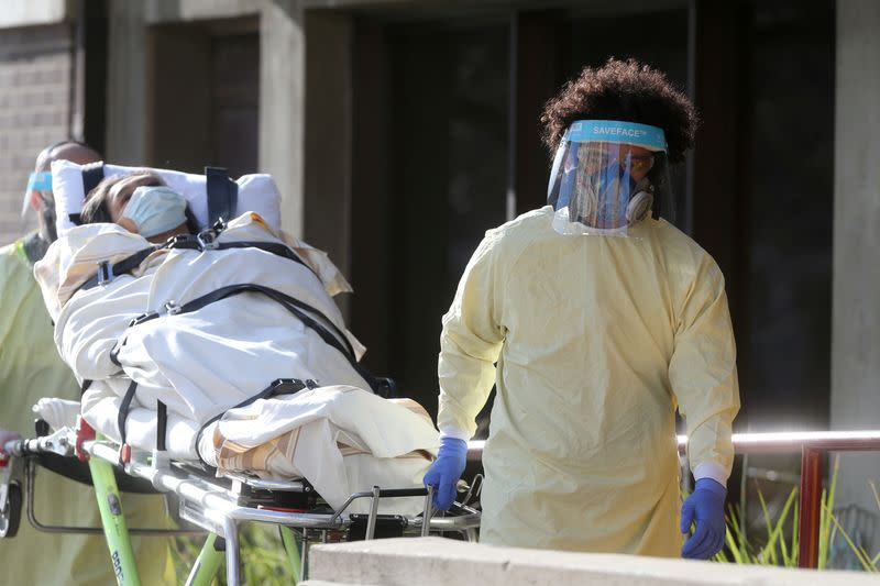 Employees of a stretcher service wear personal protective gear as they return a resident to Parkview Place personal care home, which is experiencing an outbreak of the coronavirus disease (COVID-19), in Winnipeg, Manitoba