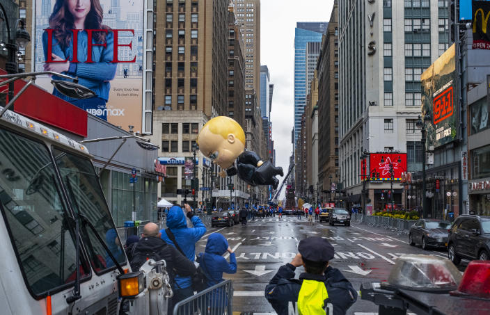 The Boss Baby balloon, viewed from a barricade two blocks away, makes an appearance during the modified Macy's Thanksgiving Day Parade in New York, Thursday, Nov. 26, 2020. Due to the pandemic, crowds of onlookers were not allowed to attend the annual parade. (AP Photo/Craig Ruttle)