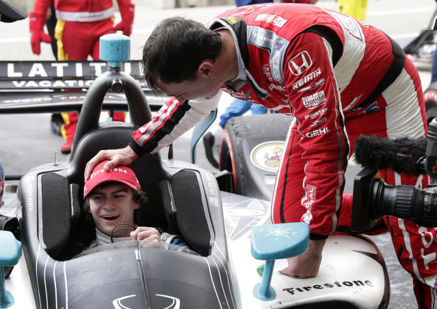 Colton Herta sits in his car on pit road as receives congratulations from Graham Rahal for winning the IndyCar Classic auto race Sunday, March 24, 2019, in Austin, Texas. Herta, 18, became the youngest driver to win an IndyCar series race. (AP Photo/Eric Gay)