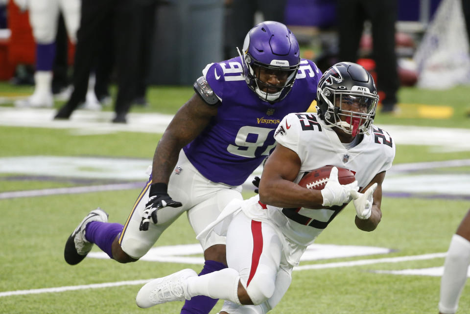 Atlanta Falcons running back Ito Smith (25) runs from Minnesota Vikings defensive end Yannick Ngakoue (91) during the first half of an NFL football game, Sunday, Oct. 18, 2020, in Minneapolis. (AP Photo/Bruce Kluckhohn)