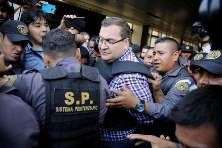 Javier Duarte, former governor of Mexican state Veracruz, is escorted by policemen while leaving a court in Guatemala City