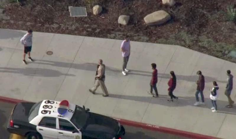 A law enforcement official leads students at the scene of a shooting at Saugus high school in Santa Clarita