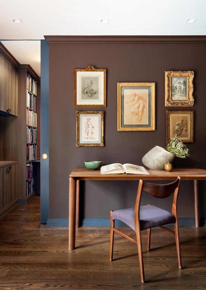 """In the library, Benjamin Moore's Appalachian Brown """"allows the Old Masters drawings to sing,"""" says Rabel. """"Dark colors work well with both Old Masters and contemporary pieces."""" A table from Stillfried Wien is paired with a vintage Danish chair and Japanese and Scandinavian ceramics."""