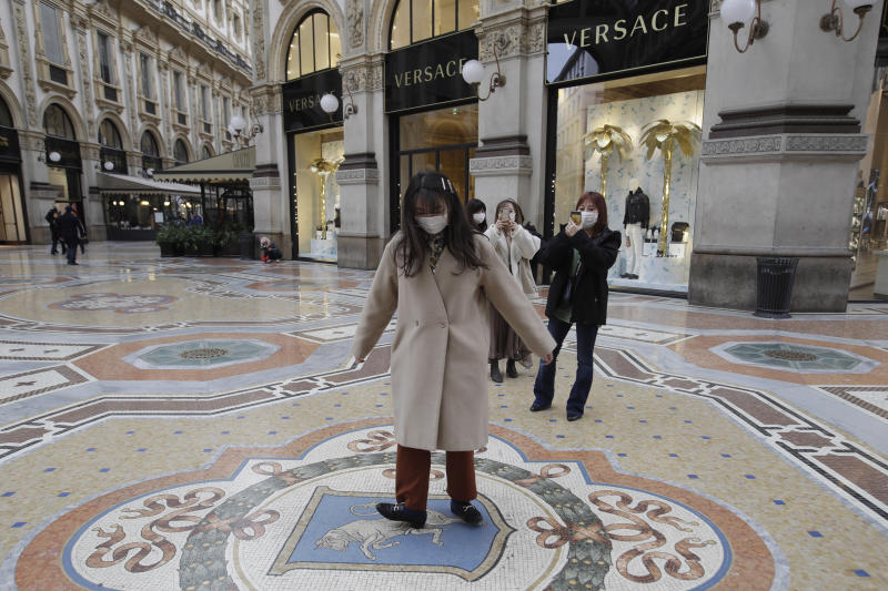 A tourist twirls around as she steps on a tiled floor mosaic depicting a bull, symbol of the city of Turin that was the first capital of the Kingdom of Italy, inside the four-story double arcade Galleria Vittorio Emanuele II, completed in 1867 and named after Italy's first king, in Milan, Italy, Thursday, Feb. 27, 2020. According to an old legend this will bring good luck and allow to return in the city. In Europe, an expanding cluster in northern Italy is eyed as a source for transmissions of the COVID-19 disease. (AP Photo/Luca Bruno)