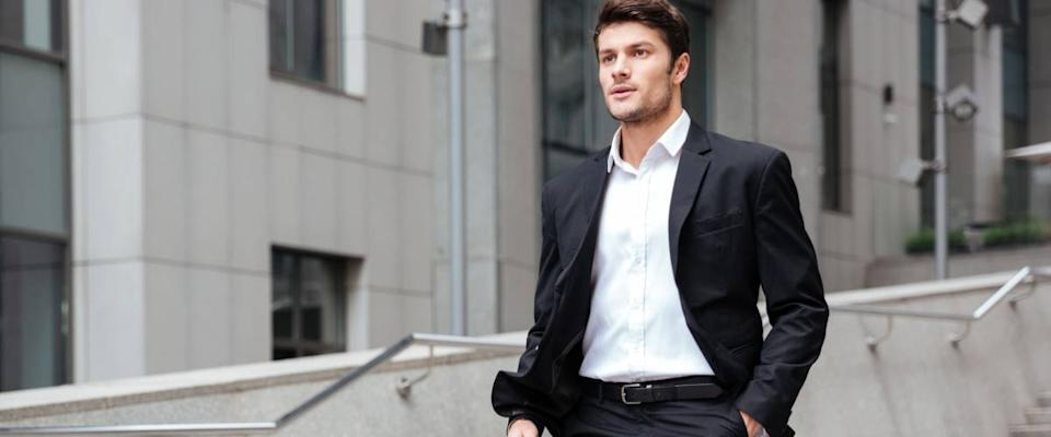Confident young businessman in suit walking on the street