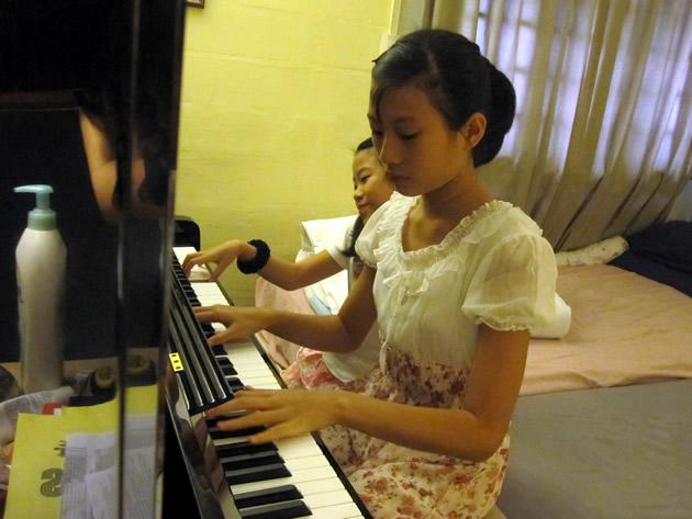 An Lyn and E Lyn (behind) Chee play a duet on the piano. They and their younger brother Shaw Hur have been playing the piano since age 5. (Yahoo! photo/Jeanette Tan)