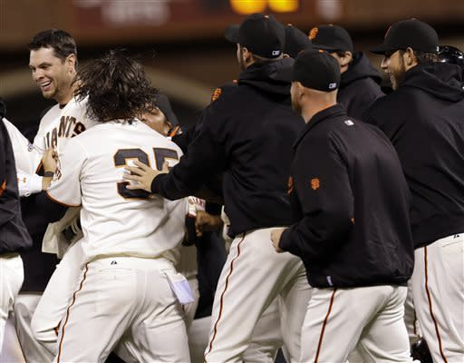 San Francisco Giants' Brandon Belt left is mobbed by teammates after driving in the game-winning run in the bottom of the ninth inning against the Arizona Diamondbacks in the bottom of the ninth inning of a baseball game against the Arizona Diamondbacks on Monday, April 22, 2013 in San Francisco. (AP Photo/Marcio Jose Sanchez)