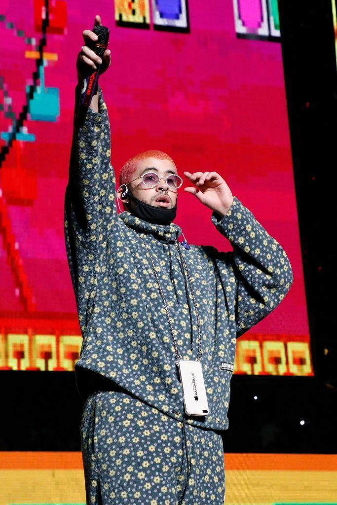 """<p>Formally known as Benito Antonio Martínez Ocasio, Bad Bunny came on to the Latin trap scene after being <a href=""""https://www.billboard.com/articles/columns/latin/8343841/bad-bunny-video-interview"""" rel=""""nofollow noopener"""" target=""""_blank"""" data-ylk=""""slk:discovered on SoundCloud"""" class=""""link rapid-noclick-resp"""">discovered on SoundCloud</a> with his song """"<a href=""""https://www.amazon.com/Diles-feat-Arcangel-Nengo-Explicit/dp/B01L0PH87Q?tag=syn-yahoo-20&ascsubtag=%5Bartid%7C10055.g.33835500%5Bsrc%7Cyahoo-us"""" rel=""""nofollow noopener"""" target=""""_blank"""" data-ylk=""""slk:Diles"""" class=""""link rapid-noclick-resp"""">Diles</a>."""" The 26-year-old Puerto Rican wrote, produced, and sang original music while <a href=""""https://www.bostonherald.com/2020/03/02/how-bad-bunny-went-from-grocery-bagger-to-rap-star/"""" rel=""""nofollow noopener"""" target=""""_blank"""" data-ylk=""""slk:bagging groceries at a supermarket"""" class=""""link rapid-noclick-resp"""">bagging groceries at a supermarket</a> in Vega Baja, Puerto Rico. Since then, he's collaborated with <strong>Drake</strong>, <strong>Cardi B</strong>., and <strong>Nicki Minaj</strong>. Not to mention, he's been <a href=""""https://www.grammy.com/grammys/artists/bad-bunny/243129"""" rel=""""nofollow noopener"""" target=""""_blank"""" data-ylk=""""slk:nominated three times"""" class=""""link rapid-noclick-resp"""">nominated three times</a> for a Grammy and performed at the 2020 Super Bowl Halftime show.</p>"""