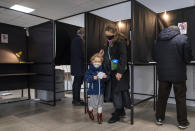 A Lithuanian family, wearing face masks to protect against coronavirus, leave a voting booth at a polling station during the second round of a parliamentary election in Vilnius, Lithuania, Sunday, Oct. 25, 2020. Polls opened Sunday for the run-off of national election in Lithuania, where the vote is expected to bring about a change of government following the first round, held on Oct. 11, which gave the three opposition, center-right parties a combined lead. (AP Photo/Mindaugas Kulbis)