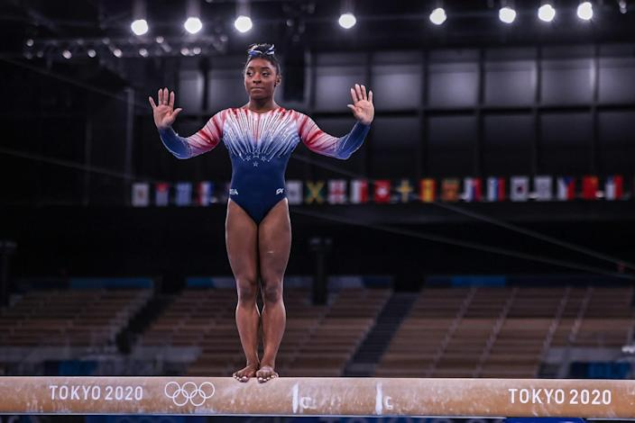 Simone Biles stands on the beam.