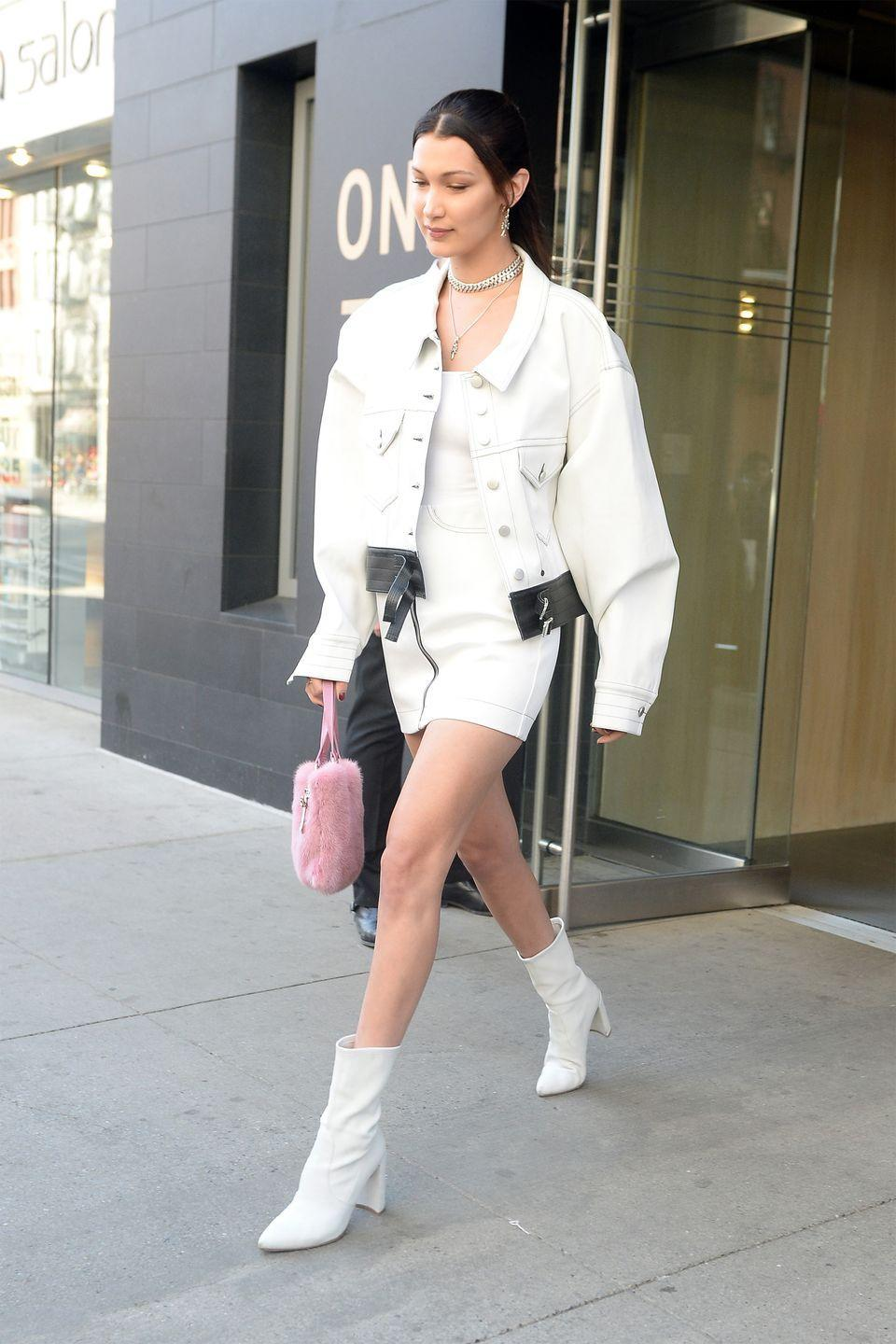 <p>In a white denim jacket with black leather detailing, tank top, zip-up miniskirt, white leather clingers, pink fur bag and silver chain while out in New York.</p>