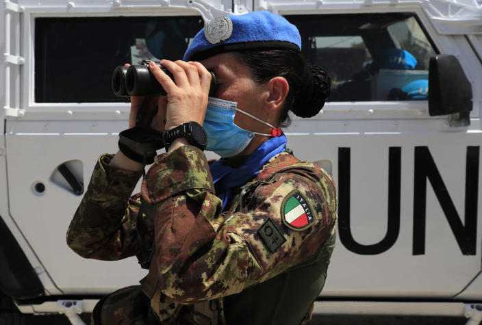 An Italian U.N. peacekeeping soldier looks through binoculars on a road that leads to a U.N. post along the border known as Ras Naqoura where Lebanese and Israeli delegations are meeting, in Naqoura, Lebanon, Tuesday, May 4, 2021. After a nearly six-month pause, Lebanon and Israel on Tuesday resumed indirect talks with U.S. mediation over their disputed maritime border. (AP Photo/Hussein Malla)