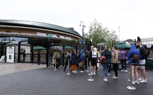 Tennis fans queue to enter the grounds on day eight of Wimbledon