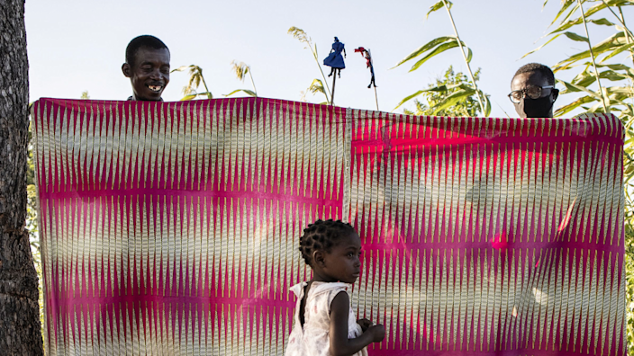 Two men put on a puppet show for children in Metuge settlement for people displaced in Mozambique - Friday 21 May 2021