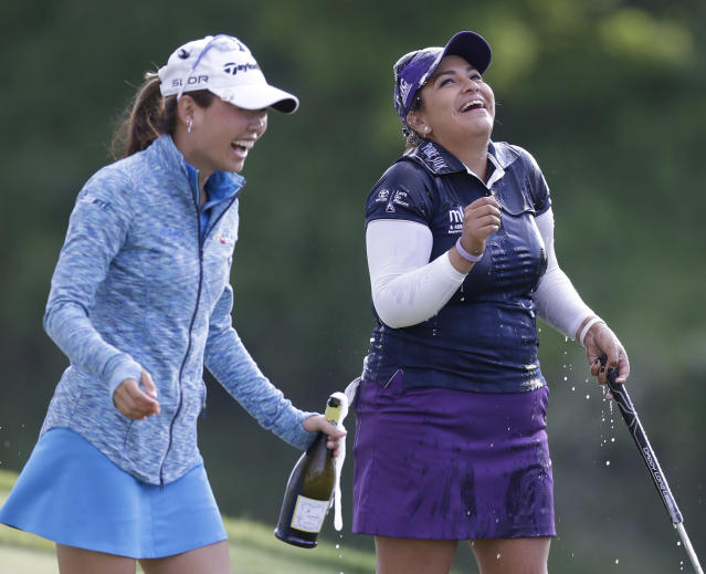 Lizette Salas celebrates winning the Kingsmill Championship golf tournament at the Kingsmill resort along with fellow golfer Nina Harigae, left, in Williamsburg, Va., Sunday, May 18, 2014. Salas won her first LPGA event after shooting an even par-71 leaving her at 13-under for the tournament. (AP Photo/Steve Helber)