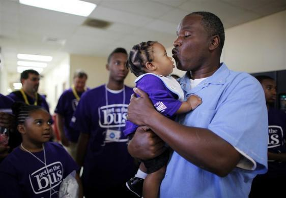 Troy (R), 43, holds his eight-month-old grandson B.J. for the first time as his niece Erika (L), 11, looks on at San Quentin state prison in San Quentin, California June 8, 2012.
