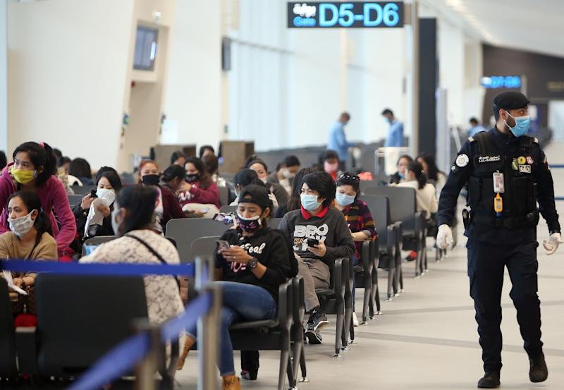FILE PHOTO: Filipinos who availed general amnesty granted by the Kuwaiti government are pictured gathering at the Kuwait International Airport Terminal 4, on April 3, 2020 on their home to Manila amid the coronavirus COVID-19 pandemic crisis. (Photo: YASSER AL-ZAYYAT/AFP via Getty Images)