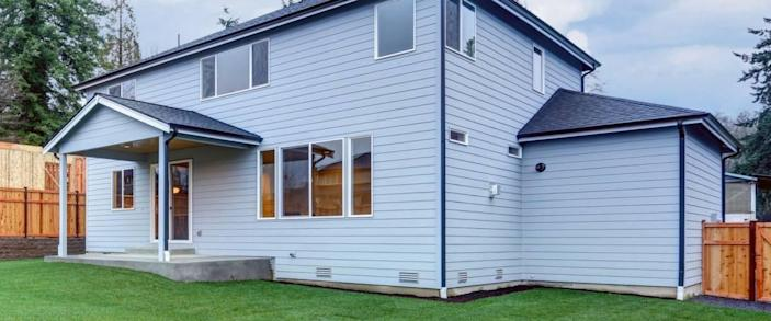 New luxury home with pale blue wood siding features covered back porch with wood plank ceiling over concrete floor. Fully fenced backyard boasts perfectly kept lawn. Northwest, USA