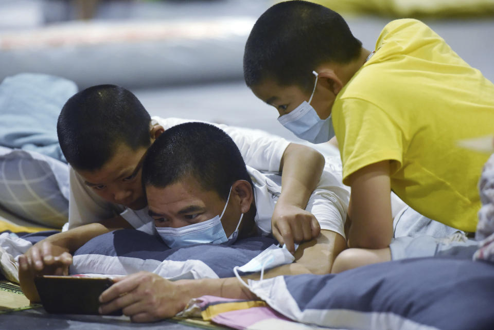 Evacuees share a mobile phone in an exhibition hall in Hangzhou in eastern China's Zhejiang province Sunday, July 25, 2021. A typhoon blew heavy rain across the Shanghai region Monday, leaving roads and low-lying areas waterlogged and felling billboards and signs on its second landfall in eastern China. (Chinatopix via AP)