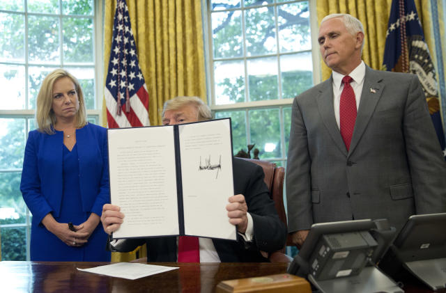 President Trump shows the executive order he signed to end family separations at the border during an event in the Oval Office of the White House on Wednesday in Washington, D.C. Homeland Security Secretary Kirstjen Nielsen and Vice President Mike Pence look on. (Photo: Pablo Martinez Monsivais/AP)