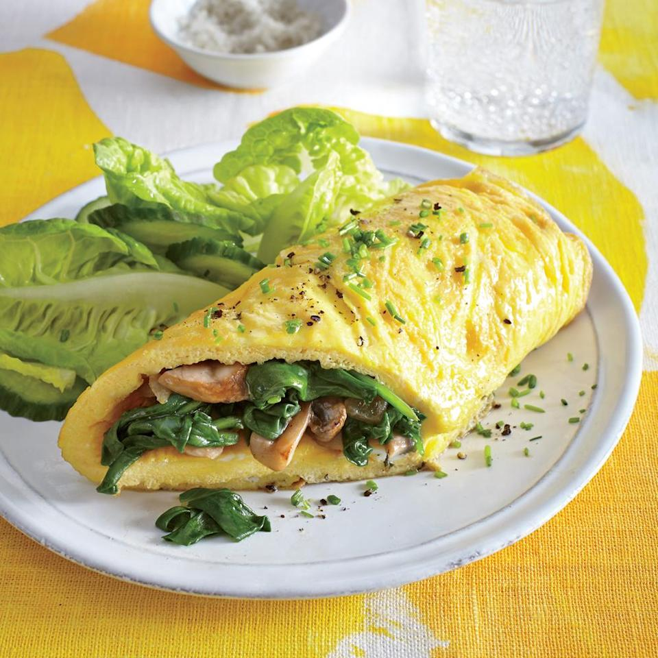 """<p>A veggie-stuffed omelet makes for one easy, satisfying dinner when paired with a simple side salad. While the <a href=""""https://www.myrecipes.com/ingredients/spinach-recipes"""" rel=""""nofollow noopener"""" target=""""_blank"""" data-ylk=""""slk:cooked spinach mixture"""" class=""""link rapid-noclick-resp"""">cooked spinach mixture</a> sits, it may give off some more liquid; strain this off to keep the omelet from becoming watery.</p>"""