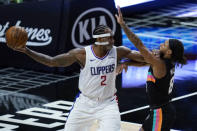 Los Angeles Clippers forward Kawhi Leonard keeps the ball away from San Antonio Spurs guard Patty Mills during the third quarter of an NBA basketball game Tuesday, Jan. 5, 2021, in Los Angeles. (AP Photo/Ashley Landis)