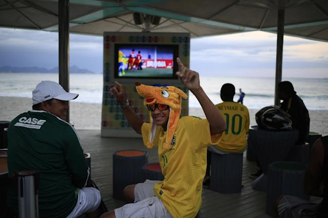Brazilian fans, one wearing a hat of the World Cup mascot Fuleco, watch a friendly soccer match between Brazil and Panama at a kiosk along Copacabana beach in Rio de Janeiro, Brazil, Tuesday, June 3, 2014. The international soccer tournament is set to begin in just a few days, with Brazil and Croatia playing in the opening match on June 12. (AP Photo/Hassan Ammar)