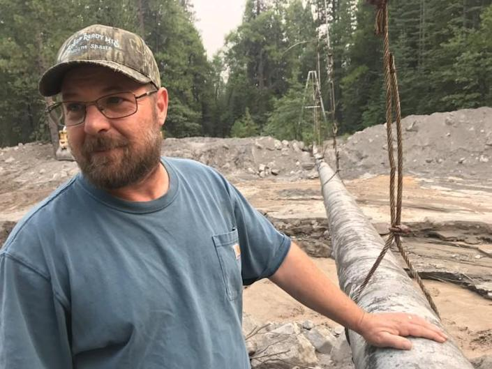 Richie Fesler, superintendent of public works for McCloud, a community of restored historic buildings on Shasta's southern flanks, is taking stock of progress being made in an effort to remove tens of thousands of cubic yards of mud that nearly buried a suspended pipeline that has supplied the area with spring water so pure it doesn't need chlorination since World War II.