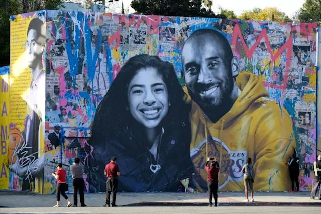 People stop to take pictures in front of the new mural by French artist Mr. Brainwash picturing Kobe Bryant and his daughter Gigi in Los Angeles on January 31, 2020. (AFP Photo/Chris Delmas)