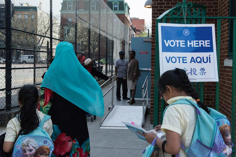A woman with a Muslim headscarf walks past a voting sign at PS 3 on April 19, 2016 in the Brooklyn borough of New York City. (Stephanie Keith/Getty Images)