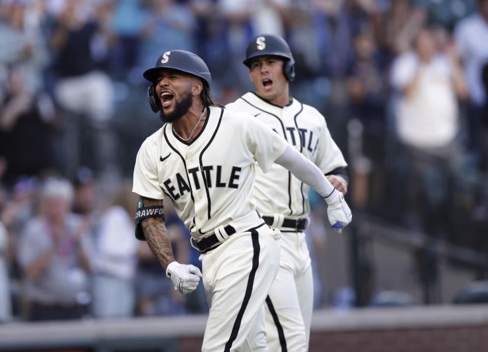 Seattle Mariners' J.P. Crawford celebrates at home with Dylan Moore behind, after hitting a grand slam off Tampa Bay Rays starting pitcher Josh Fleming during the second inning of a baseball game Saturday, June 19, 2021, in Seattle. (AP Photo/John Froschauer)