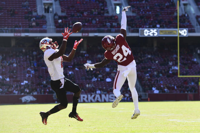 Western Kentucky receiver Lucky Jackson makes a catch in front of Arkansas defender LaDarrius Bishop to set up a touchdown during the first half of an NCAA college football game, Saturday, Nov. 9, 2019 in Fayetteville, Ark. (AP Photo/Michael Woods)