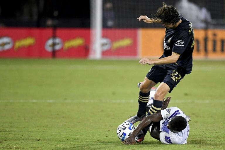 Orlando City SC's Sebas Mendez (bottom)  tackles Brenden Aaronson (22) of Philadelphia Union during the second half in the MLS is Back Tournament at Wide World of Sports Complex