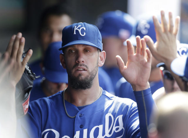 Kansas City Royals starting pitcher James Shields is congratulated by teammates in the dugout during the ninth inning of a baseball game against the Cleveland Indians, Wednesday, Sept. 11, 2013, in Cleveland. Shields pitched 8 innings and gave up four hits and two runs. The Royals won 6-2. (AP Photo/Tony Dejak)