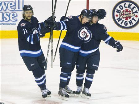 Winnipeg Jets Scott Kosmachuk (C) celebrates with team mates Nic Petan (R) and Julian Melchiori after he scored against the Washington Capitals in the second period of their NHL pre-season hockey game in Belleville Ontario September 14, 2013. REUTERS/Fred Thornhill